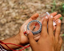 Close-up of a student's hands navigating with a compass.